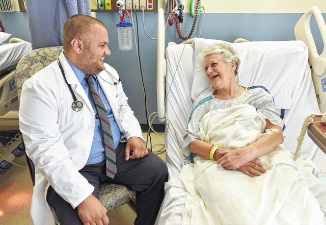 Homegrown physician Dr. Kevin Musto visits with patient Walburga Pileggi of Clifford at the Community Medical Center in Scranton. She was the first patient he saw on July 1, just as he was beginning his second year of residency.
