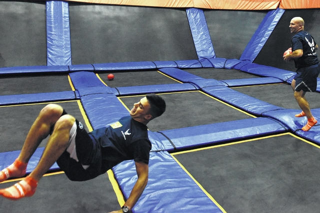 Air Force Tech Sargeant Dominck Aritz throws the ball at his opponents while his teammate Alexander Baney goes airborne in the dodgeball tournament at Sky Zone Trampoline Park in Jenkins Township on Monday.