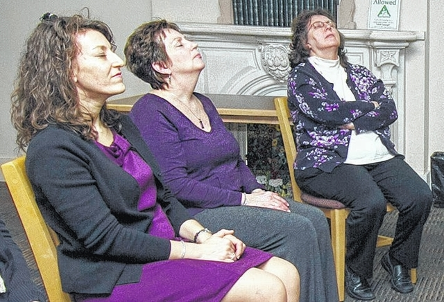 Melissa Werner of Laflin, Carol Dalmas of Nanticoke and Debbie Augustine of Kingston participate in a relaxation exercise during Chris Halbohm's presentation at the Hoyt Library in Kingston.
