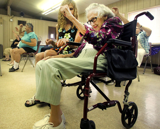 Mary Buczynski tries to stretch her arms during an exercise while her daughter, Francine Buczyski, sits next to her. The exercise class at the Edwardsville Senior Center.