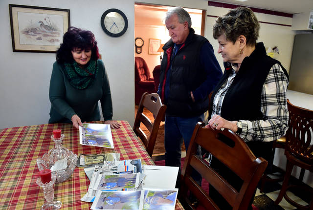 Joe Lloyd's siblings — from left, Barbara Walton of Larksville, John Leo Lloyd of Pittston, and Maryalice James of Edwardsville — look through old photos of Joe at James' home last week. Joe died on Jan. 25, two days after suffering a series of three heart attacks. (Sean McKeag | Times Leader)