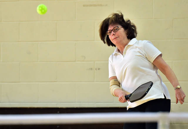 Beth Rosenthal, of Shavertown, volleys the ball over the net during a game of pickleball at the Wilkes-Barre Family YMCA March 3. Rosenthal said the game can be fun for the whole family and that she has played with her daughter.