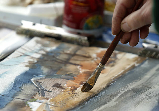 Tim Weaver, of Drums, works on a watercolor painting at his booth at the Fine Arts Fiesta on Sunday, the final day of the four-day event.