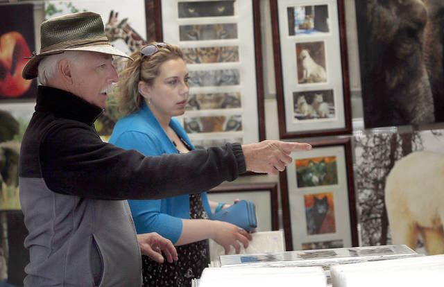 Ted Schiffman, of Vermont, points out photos to Joanna Smith, of Dallas, in his Ted Schiffman Productions booth at the Fine Arts Fiesta in Wilkes-Barre on Sunday. Smith bought several pieces from Schiffman.