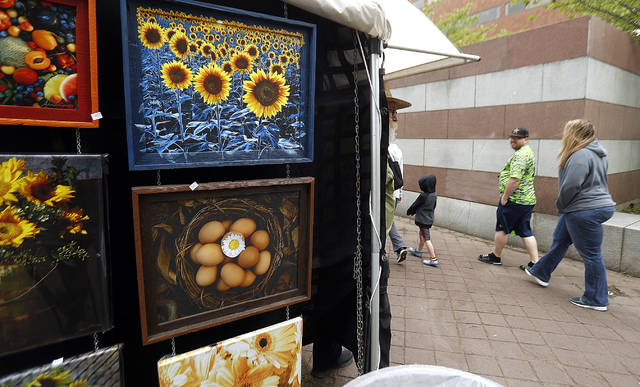 Visitors to the Fine Arts Fiesta walk past a booth on the final day of the event Sunday.