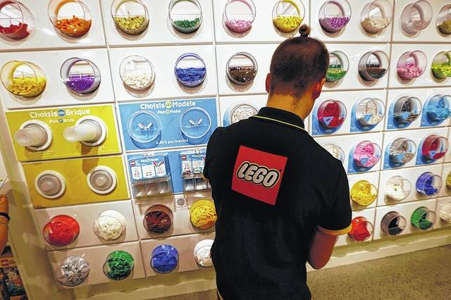 In this 2016 file photo, an employee sorts Legos in the the new Lego flagship store in Paris. Danish toy maker Lego said Tuesday it will cut 1,400 jobs, or about 8 percent of its global workforce, after reporting a decline in sales and profits in the first half of 2017.