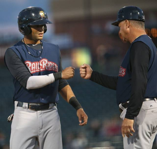 Mason Williams celebrates with manager Al Pedrique after scoring the opening run of Friday night's playoff game.