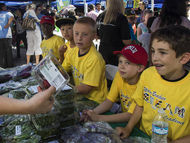 Walter Bracken Elementary students talk radishes with a customer during the farmers market.