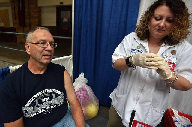 Michael Hischak waits to receive a flu shot from Jennifer Richards, a pharmacy manager at Rite Aid, during the Senior Expo at the Kingston Armory on Thursday.