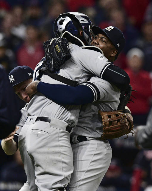 New York Yankees relief pitcher Aroldis Chapman hugs catcher Gary Sanchez after the Yankees defeated the Cleveland Indians 5-2 in Game 5 of a baseball American League Division Series, Wednesday, Oct. 11, 2017, in Cleveland. The Yankees advanced to the ALCS. (AP Photo/David Dermer)