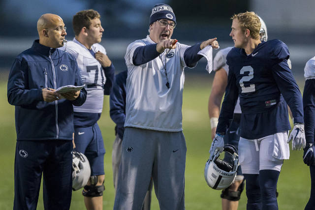 Penn State head coach James Franklin, left, looks on as offensive coordinator Joe Moorhead talks with quarterback Tommy Stevensduring football practice, Wednesday, Oct. 25, 2017 in State College, Pa. (Joe Hermitt/PennLive.com via AP)