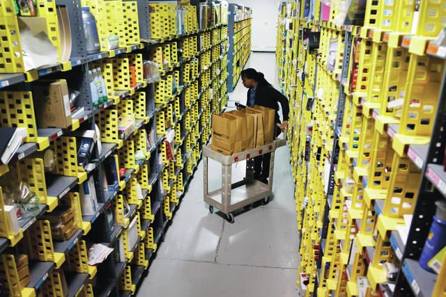 Amazon Prime employee Alicia Jackson hunts for items at the company's urban fulfillment facility t in New York.