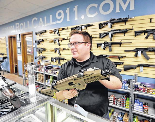 Roll Call 911 sales associate Jerry Dougherty describes a CZ Scorpion pistol to a customer.