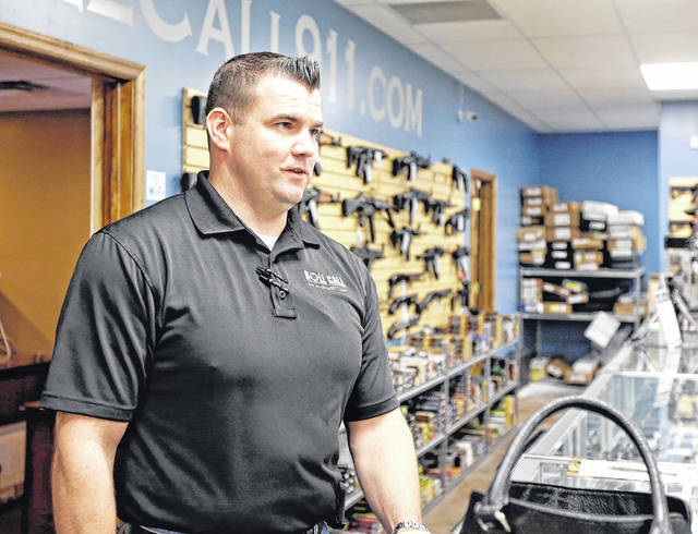 Roll Call 911 co-owner Joe Harris talks with a customer at the shop on Hudson Avenue in Scranton.