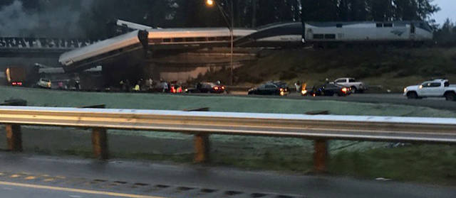 """This photo provided by Danae Orlob shows an Amtrak train that derailed south of Seattle on Monday, Dec. 18, 2017. Authorities reported """"injuries and casualties."""" The train derailed about 40 miles (64 kilometers) south of Seattle before 8 a.m., spilling at least one train car on to busy Interstate 5. (Danae Orlob via AP)"""
