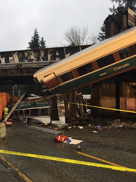 """This photo provided by Washington State Patrol shows an Amtrak train that derailed south of Seattle on Monday, Dec. 18, 2017. Authorities reported """"injuries and casualties."""" The train derailed about 40 miles (64 kilometers) south of Seattle before 8 a.m., spilling at least one train car on to busy Interstate 5. (Washington State Patrol via AP)"""