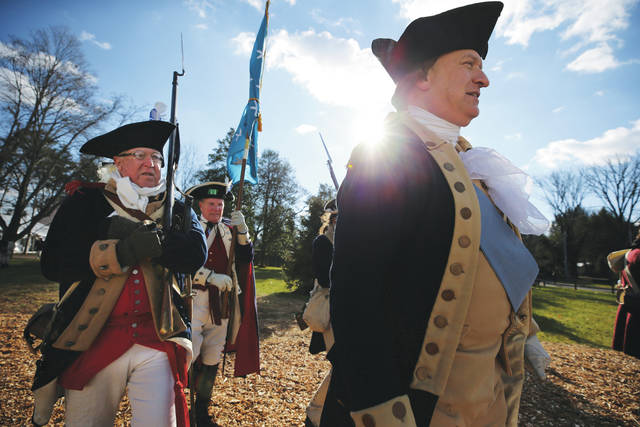 John Godzieba, as Gen. George Washington, right, marches with his troops during a re-enactment of Washington's daring Christmas 1776 crossing of the Delaware River on Monday in Washington Crossing. High winds scuttled the annual re-enactment of George Washington's crossing of the Delaware River during the Revolutionary War. Other activities went on as scheduled, including Washington's rallying of his troops, historical speeches and processions.