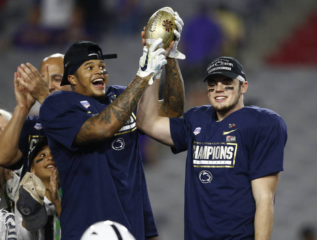 Penn State captains Marcus Allen and Trace McSorley hold up the top of the Fiesta Bowl trophy after holding off Washington on Saturday.