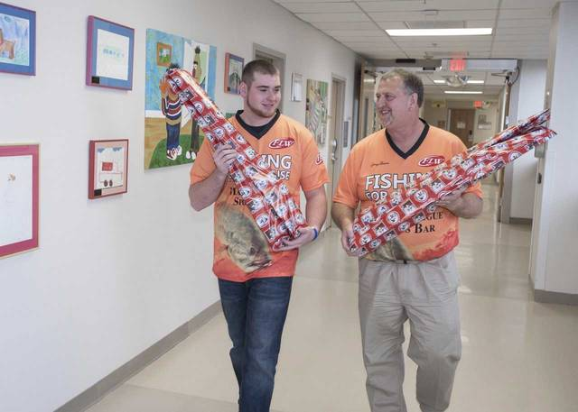 George Bowers, right, and his son, Connor, deliver fishing rods and reels as presents to children at Geisinger Wyoming Valley on Tuesday. Bowers and his son have been donating the gifts to hospitalized children before Christmas for the last 17 years.