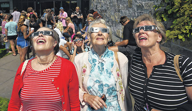 From left, MajBritt Black, of Michigan, and her mother and sister, Lisbeth Nilsson and Marian Heintz, of Dallas, watch the solar eclipse at the Penn State Lehman campus in August.
