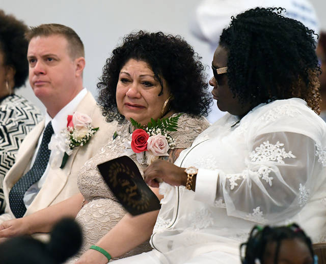 Susan Major, center, is surrounded by brother Sal Bellanco and friend Sharee Clark during the funeral for Major's three children, Erik DuPree, Devon Major and Ezekiel Major, who died in October as a result of a fire at the family home in Laflin.