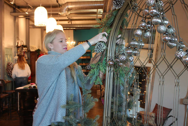 Jamie Flack fixes a mirror display inside Rustique at the 900 Rutter complex.