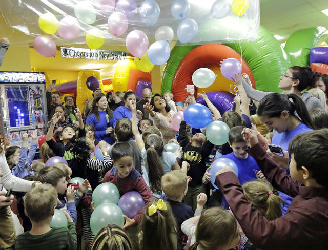 Children and their parents celebrate a 'Countdown to Noon' with a balloon drop at Super Bounce in Wyoming on Sunday.
