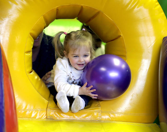 Two-year-old Grace Dudkowski, of Drums, gets ready to go down an inflatable slide with her balloon at 'Countdown to Noon' at Super Bounce in Wyoming on Sunday.