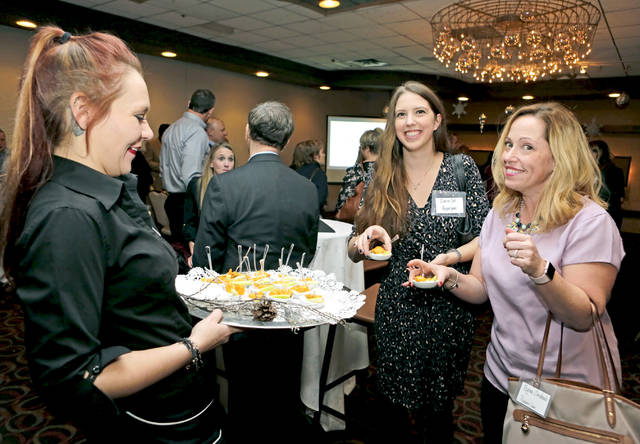 Regina Corchado, right, and Daina Cali, both of Pepperjam in Wilkes-Barre, take appetizers Tuesday from Woodlands Inn server Cassy Giarratano at the inaugual 'NEPA Best Places to Work' event sponsored by the Times Leader Media Group.