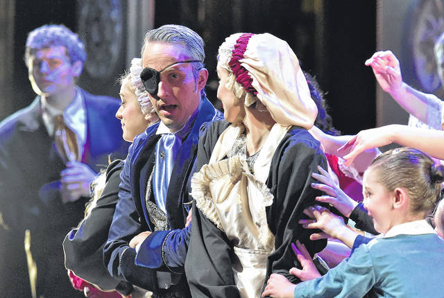 Guest artist TJ Firneno, wearing the eyepatch and flanked by two dancers who are portraying maids, supplies magic and mystery in his role as Uncle Drosselmeier.