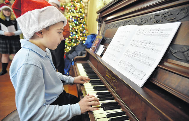 Nathan Orlando from Wyoming Area Catholic School plays an instrumental version of 'Silent Night' for the residents of Wesley Village on Wednesday morning in Jenkins Township.