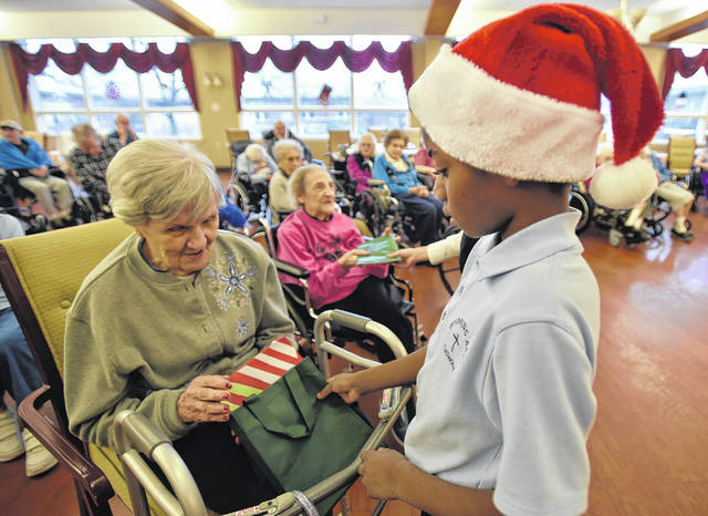 Wyoming Area Catholic student Christian Renfer gives Wesley Village resident Melinda Pirillo a handmade gift after the caroling session.