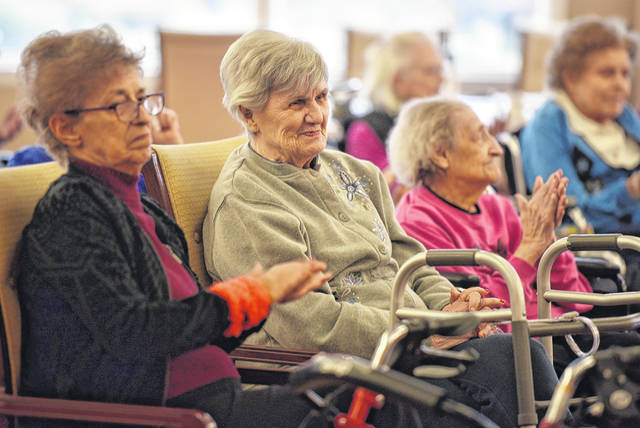 Rose Seroka, left, and other residents of Wesley Village listen to the concert given by students from Wyoming Area Catholic School.