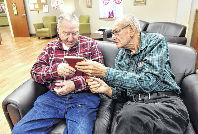 Military veterans John Ciliberto, 70, and Daniel Mazeroski, 80, look at a photograph of when Ciliberto, left, was 21 years old in basic training.