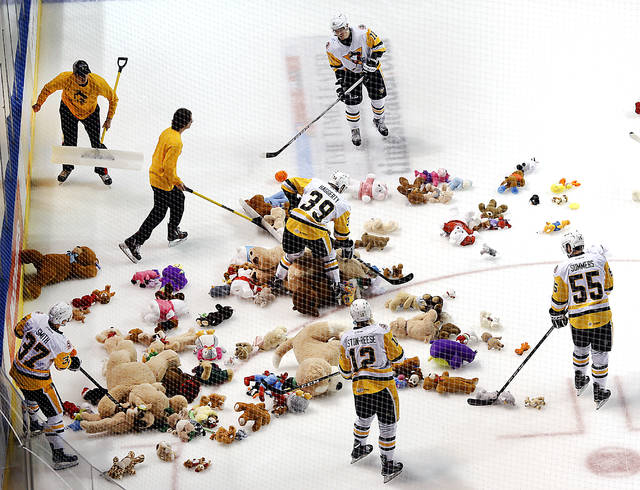 Penguins players and ice crew gather up teddy bears after their first goal against Rochester as part of the Teddy Bear Toss on Saturday at Mohegan Sun Arena.