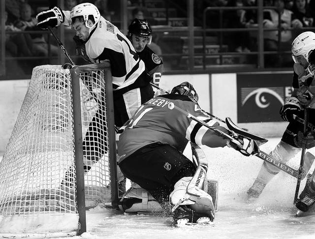Penguins Gage Quinney gets hit from behind by Binghamton defenseman Colton White as he tries to get the puck past goalie Ken Appleby during Friday's game.