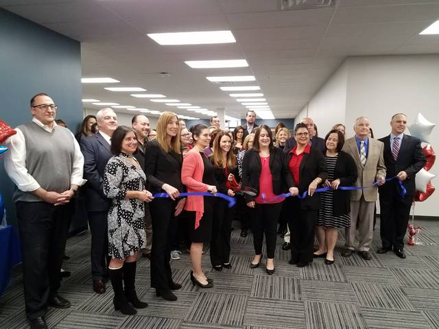 Maria Scagliotti, director of the Cintas National Accounts Fire Center, cuts the ribbon Tuesday to mark the opening of Cintas' new location in CenterPoint East in Pittston Township. She's flanked by other Cintas employees. The new center will be the company's hub for working with customer invoices.