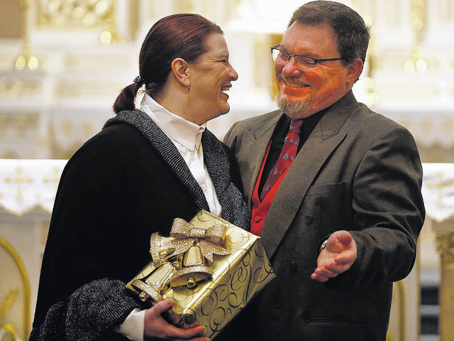 Lucy Singer and Scott Singer are married in real life and they play a married couple, Suzette and Jack, in 'The Gold Wrapping Paper,' a Christmas play written by the Rev. Gerald Gurka. This play is not as lighthearted as some of the priest's previous plays. 'It's very different; that's for sure,' Lucy Singer said.
