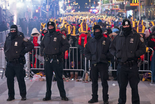 New York City police officers stand near revelers gathered on Times Square in New York Sunday, Dec. 31, 2017, during a New Year's Eve celebration. (AP Photo/Craig Ruttle)