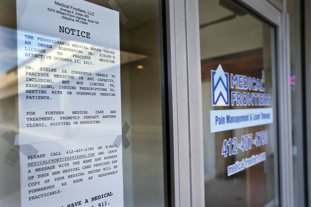 A notice stating the license to practice medicine for Dr. Andrzej Zielke has been suspended, is posted on the door at the closed Medical Frontiers office in Gibsonia.