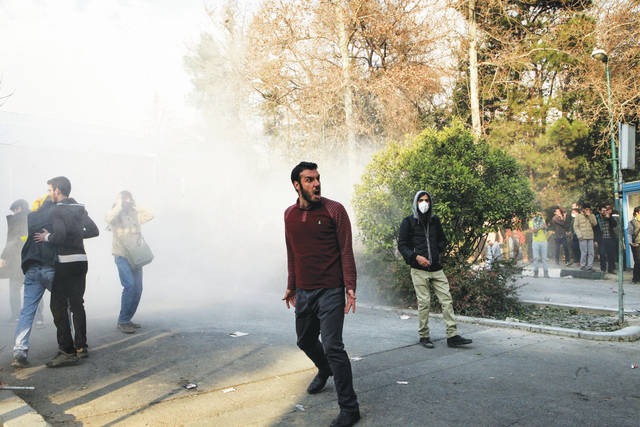 In this photo taken by an individual not employed by the Associated Press and obtained by the AP outside Iran, university students attend a protest inside Tehran University while a smoke grenade is thrown by anti-riot Iranian police, in Tehran, Iran, on Saturday.