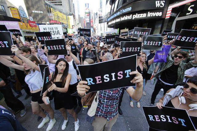FILE - In a Wednesday, July 26, 2017 file photo, demonstrators gather in Times Square, in New York to protest after President Donald Trump declared a ban on transgender troops serving anywhere in the U.S. military. The Justice Department has put its proposed ban on transgender military recruits on hold, meaning their enlistment can start Monday, Jan. 1, 2017. But the future for transgender people in the armed forces remains murky.  (AP Photo/Frank Franklin II, File)