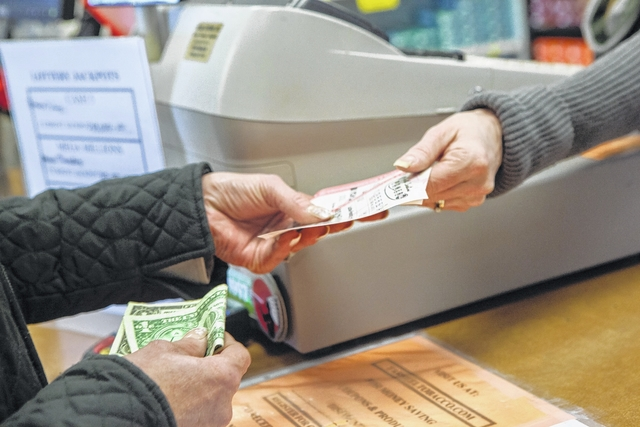 A customer holds tickets for the North Carolina Powerball at Tar Heel Tobacco on Rockford Street for a Jan. 6 jackpot of $500 million.  The jackpot for the lottery reached $1.5 billion by Tuesday afternoon.