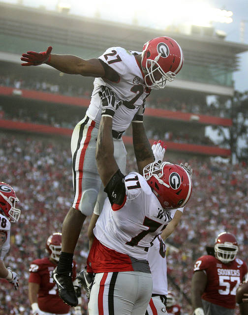 Georgia tailback Nick Chubb is hoisted in the air by Isaiah Wynn after scoring a touchdown against Oklahoma during the second half of the Rose Bowl NCAA college football game Monday, Jan. 1, 2018, in Pasadena, Calif. Georgia won 54-48. (Curtis Compton/Atlanta Journal-Constitution via AP)