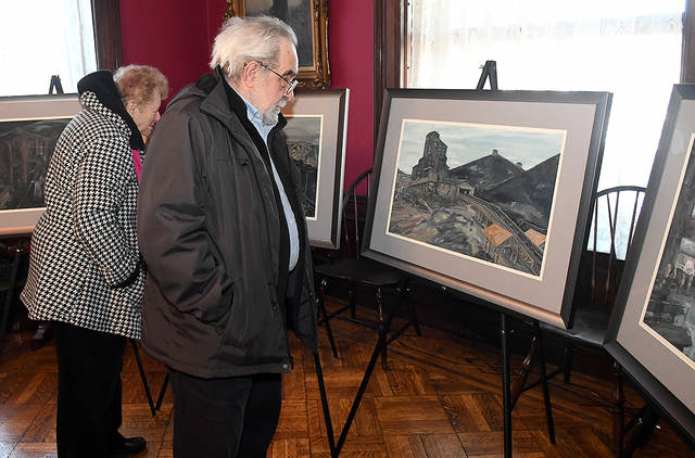 Lillian and Joseph Caffery, of Larksville, look over mining artwork done my artist Remo Trieste Russo prior to the start of a program at the Catlin House in Scranton on Sunday.