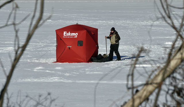 A lone ice fisherman checks his lines at the Frances Slocum Lake on Tuesday morning, the bitter cold tems are sticking with us through the weekend. Aimee Dilger | Times Leader