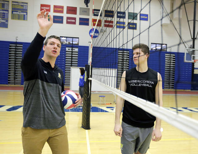 Misericordia men's volleyball coach Robert Wingert, left, instructs junior setter Bailey Brugler during practice. Brugler was on the Misericordia basketball team his first two years at the school.