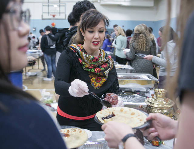 Allison Lyavdansky serves up Russian blini with jam during the 24th annual Wyoming Seminary International Dinner on Saturday at the school in Kingston.