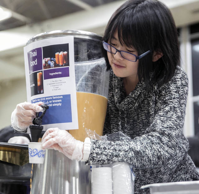 Nancy Chen, a Wyoming Seminary student from China, pours some Thailand iced tea.
