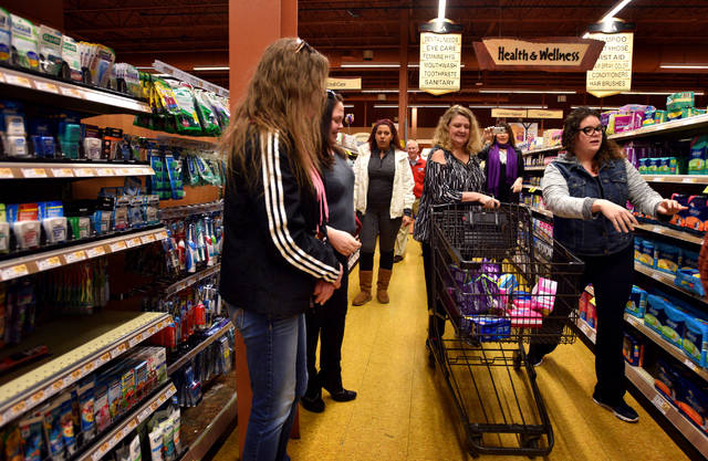Nicole Shields grabs feminine hygiene products off the shelves at Wegmans as her aunt, Anne Opiela, pushes the shopping cart during the United Way/Wegmans Shopping Spree. Opiela, an employee at Berkshire Hathaway GUARD, won the shopping prize from the United Way and in turn donated her winnings to Ruth's Place.